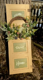 Vertical sign with spring wreath that says Home Sweet Home