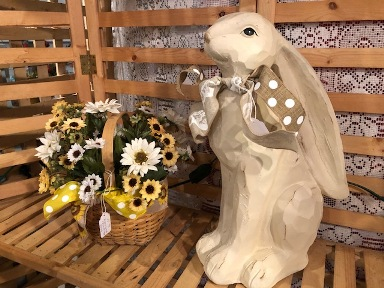 Tall resin bunny with bow and basket of white and yellow flowers