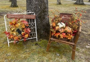 White fence gate with wreat, crow and Harvest Your Blessings sign and chair with floral arrangement and  Harvest sign