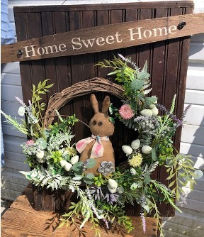 Wooden wall hanging with wreath, flowers and bunny on it.