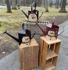 Watering cans with snowmen painted on them